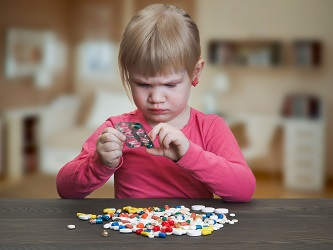 Child playing with pills